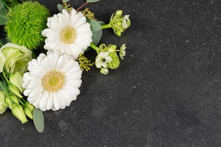 White fresh flowers on granite tombstone background. Funeral and condolences theme.