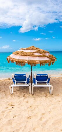 Two chairs and umbrella on the tropical beach of Mullet Bay, Sint Maarten, Caribbean.