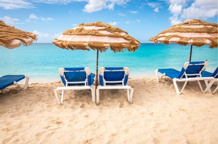 Beach chairs and umbrella on a white sandy beach in Sint Maarten, the Caribbean. Summer vacation concept. Фото со стока