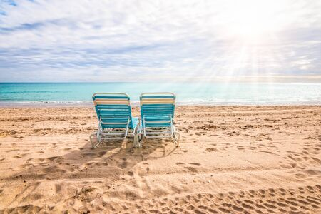 Two empty beach chairs on the beach of Hollywood, Florida. Фото со стока - 150353686