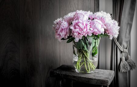 Pink peonies in vase on rustic wooden table. Romantic home decoration.