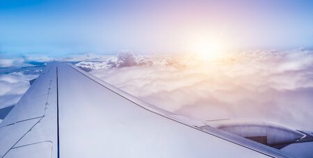 Wing of airplane above the clouds at sunrise. Фото со стока - 149919915