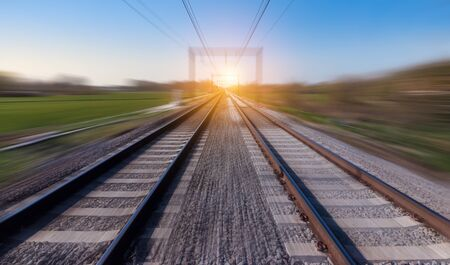 Railway track in motion. Blurred rail landscape at sunset.