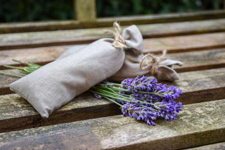 Fresh lavender flowers and canvas fragrant bag with dried lavender flowers on rustic wooden bench.