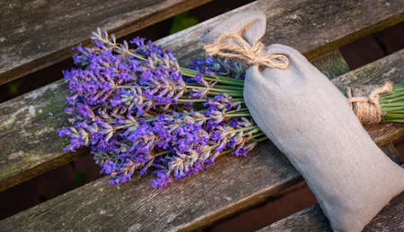 Bunch of fresh lavender flowers and scented flower sachet on wood. Фото со стока