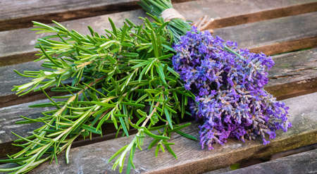 A bunch of fresh lavender and rosemary on a wooden garden table.