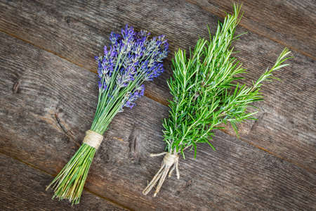 Aromatic and homeopathic herbs. Lavender and rosemary bundles on a wooden table.