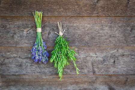 Bundles of fresh lavender flowers and rosemary herbs against a wooden wall.
