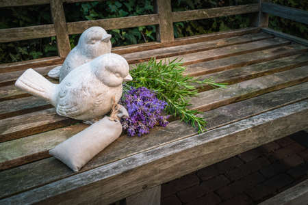 Garden bench decorated with stone birds and aromatic herbs in summertime.