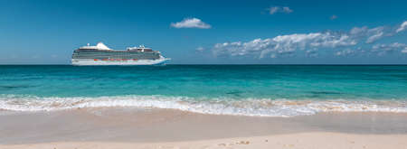 Side view of luxurious cruise ship at the beautiful white sand beach of the Cayman Islands in the Caribbean.