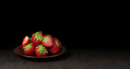 A brown plate with fresh red juicy strawberries from Belgium isolated against a dark background with space for text. Фото со стока - 151992873