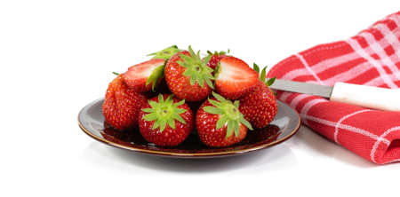 A brown bowl of fresh juicy strawberries and a knife on a red kitchen towel against a white background. Фото со стока - 151992883