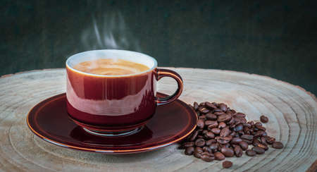Hot steaming espresso coffee in a brown vintage cup and fresh coffee beans next to it on a rustic wooden surface. Beverages concept with a dark background. Фото со стока - 152101334