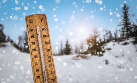 Wooden thermometer against a snowy winter landscape background. Cold temperatures with extreme winter weather concept.