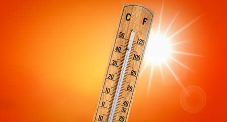 Thermometer against orange background with hot summer sun. Heat wave concept.