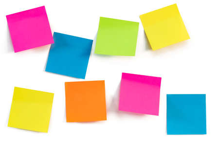 Colorful sticky notes isolated against a white wall. Close up. Space for ideas or messages.