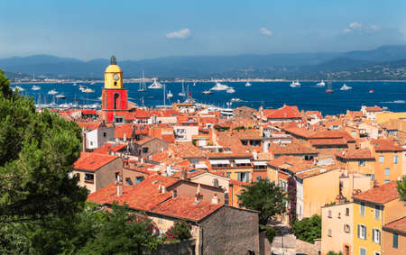 Old town of Saint Tropez with colorful church tower and typical houses with red roofs. Фото со стока
