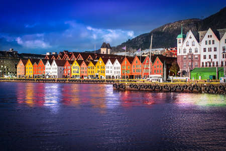 Bryggen in Bergen at night. Traditional colorful wooden houses on the quayside of the historic harbor district. Famous landmark in Norway. Фото со стока