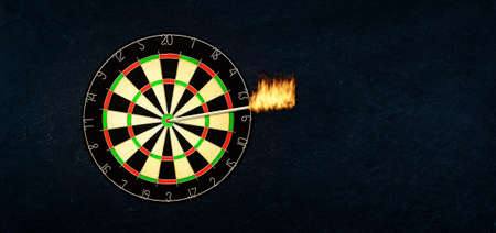 Success and business concept: Dartboard with burning arrow in the bulls eye or the target.