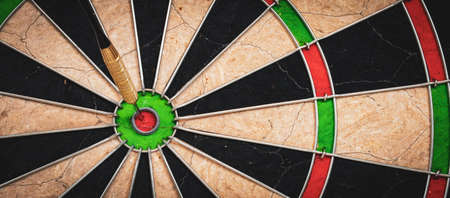 Success and business target concept: Close view of dartboard with dart in the bulls eye.