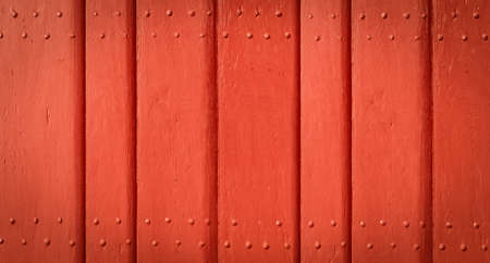Red painted wooden exterior door. Detail of solid wood planks with nails. Фото со стока