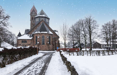 Catholic parish church and snowy street in Butgenbach, Ardennes, Belgium.