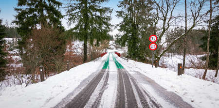 Snow covered road and narrow bridge with traffic signs in Butgenbach, Ardennes, Belgium.