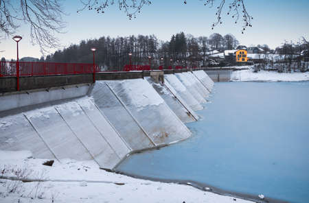 Dam at frozen lake in Bütgenbach, Ardennes, Belgium. Фото со стока