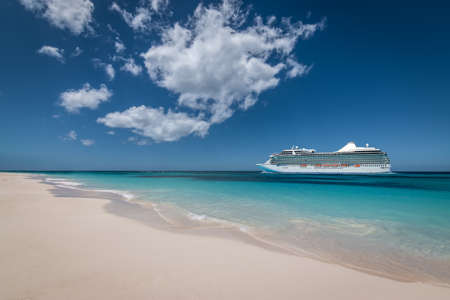 Summer cruise vacation and tourism concept. Side view of cruise ship at the beach.