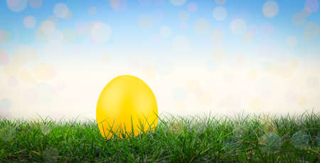 Yellow Easter egg in grass. Easter background. Фото со стока