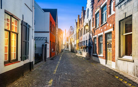 Narrow street with traditional houses in medieval city center of Bruges, Belgium.