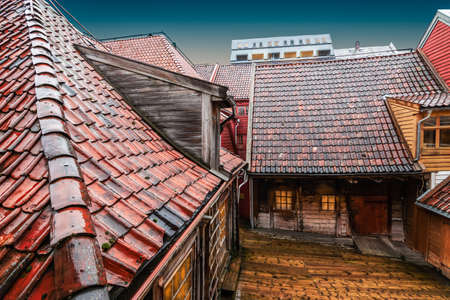 Wet roofs of old wooden buildings in Bryggen district, Bergen, Norway. Фото со стока