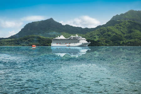 Luxurious cruise ship reflecting in the waters of a beautiful bay of the Leeward Islands in French Polynesia.