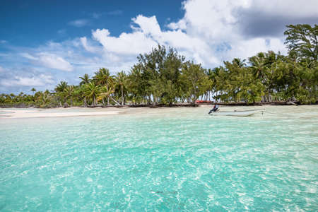 Atoll of Fakarava Island with small anchored boat at beautiful palm tree beach in French Polynesia.