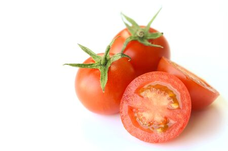 Fresh red tomatoes isolated with half cut on white background. Stock Photo