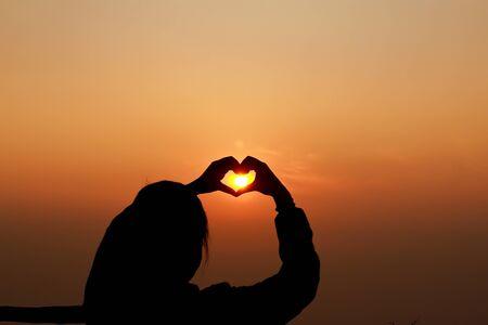 Hands make heart shape before Sunrise . photo