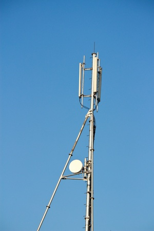 Modern cell and antenna with flat parabola on blue sky Stock Photo