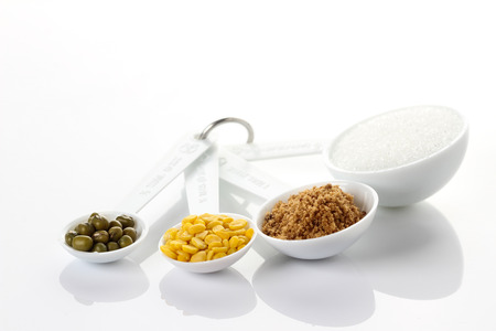 Beans in measuring spoons on white background photo