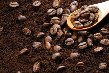 coffee beans in spoon on ground coffee photo