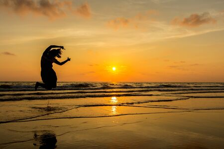 Happy Woman Jumping in Sea Sunset photo