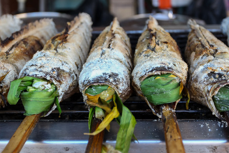 snakehead: fresh delicious grilled fish Striped snakehead fish with salt. dark burn skin with charcoal outdoor for sale on street market in THAILAND