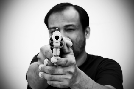 selectively: black and white of man holding gun and pointing his gun revolver. Selectively concentrated on the front of the gun.