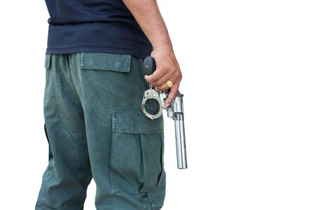 man standing and hand holding gun revolver ,side view on gray background