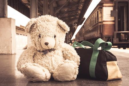 children playing: vintage tone, teddy bear sitting alone at Railway Platform Stock Photo
