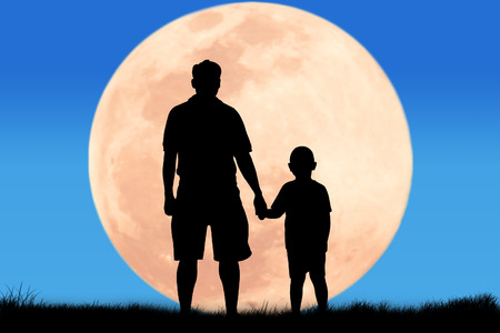 shadow silhouette: silhouette father hand hold his son looking forward at the full moon background Stock Photo