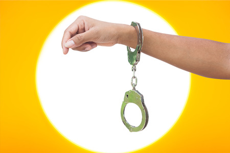 shackle: hand women in shackle on light and yellow background