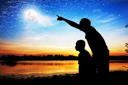 Silhouette of father use hand point his son look at meteor shower and star on the sky