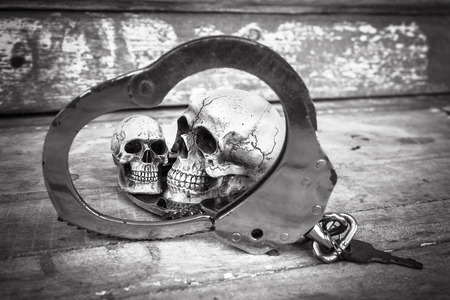 in bondage: still life and vintage of skull human with handcuff on old wooden  background Stock Photo