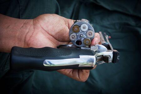 holding gun: hand man holding show gun  storage cylinder .357 magmun of revolver handgun