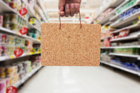 insider information: hand hold  empty brown cork board for insert text insider information in the supermarket